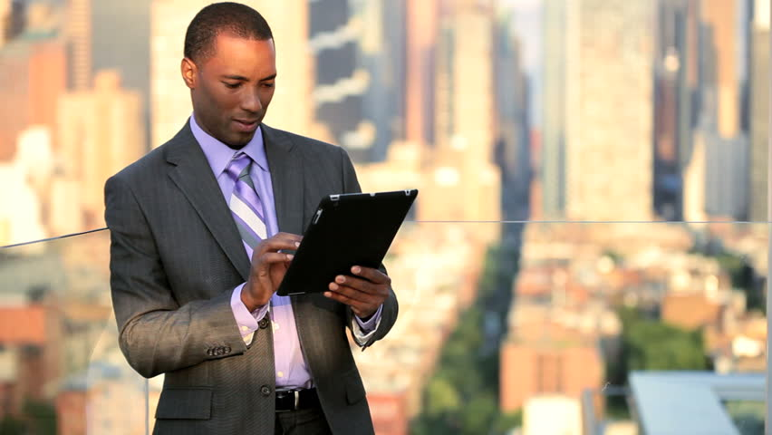 African American male business manager on a tablet overlooking Manhattan