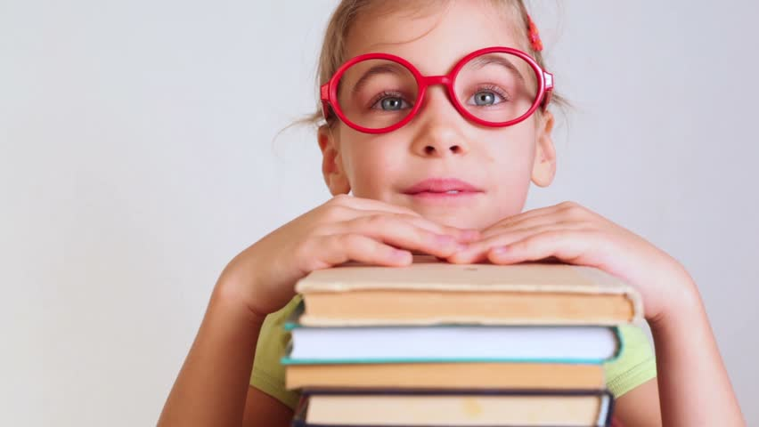 a little girl in red glasses lies on the pile of books