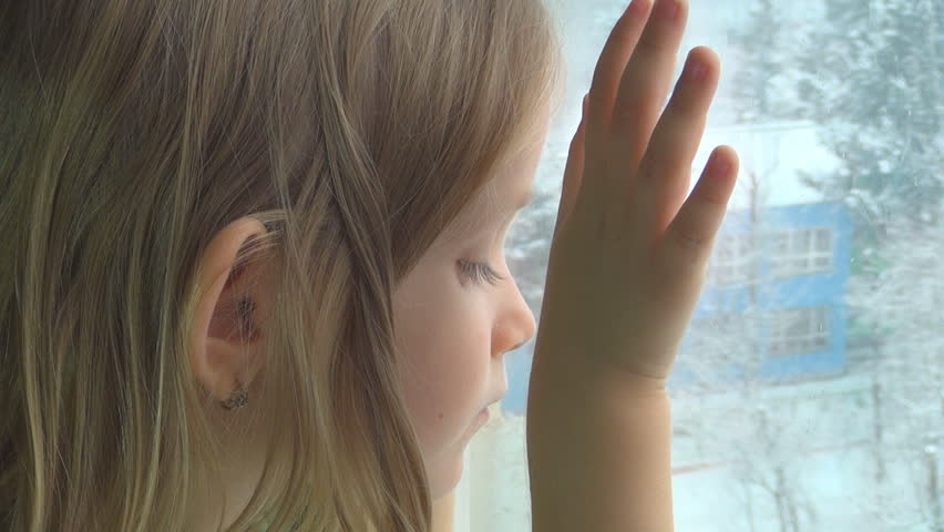 Sad Child Looking Out the Window,  It's Snowing Outdoor, Depressed Little Girl  - HD stock footage clip