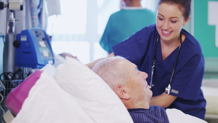 A beautiful female nurse attends to an elderly male patient, plumping up his pillows and chatting with him. In slow motion.