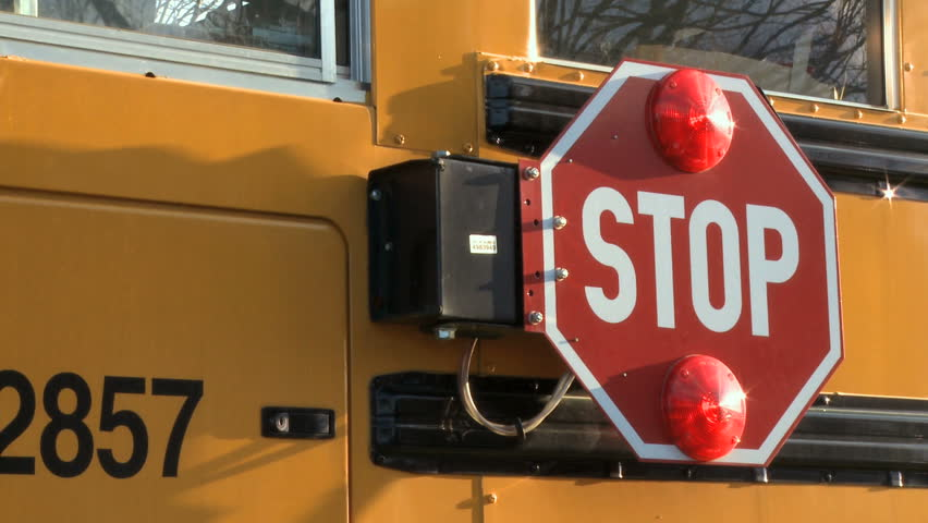 Two takes of the stop sign on a school bus swinging out to signal drivers to stop for school children. - HD stock footage clip