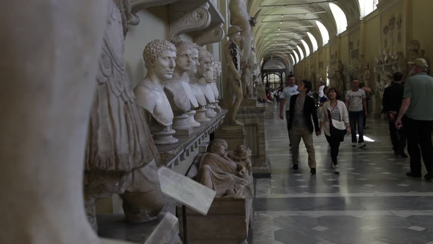 VATICAN CITY - MAY 5, 2012: A couple walks down the Gallery of Busts in the Vatican Museum, stopping to look at a plaque  - HD stock footage clip