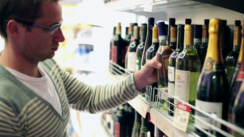 Young man choosing wine in the shop, steadycam shot