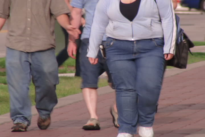 Obese people walking down urban street. - SD stock video clip