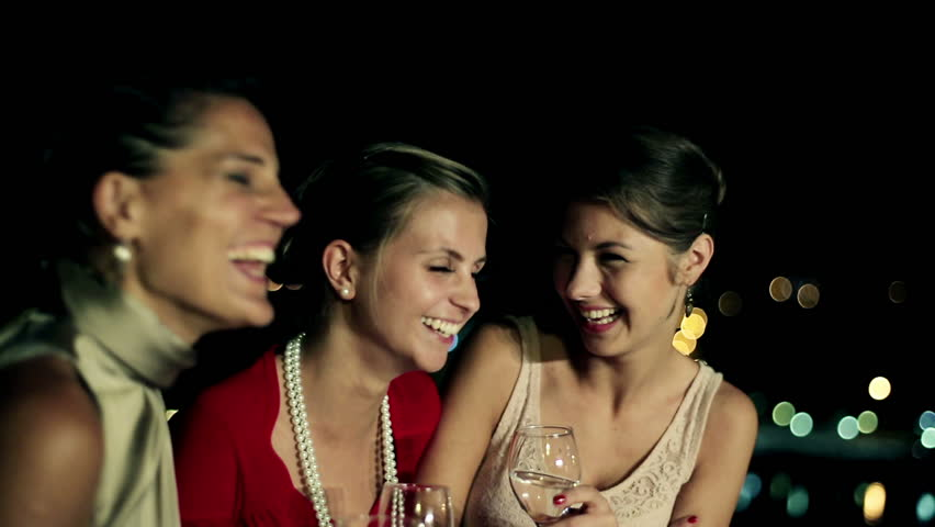 Three female friends enjoying night party on the terrace, crane shot