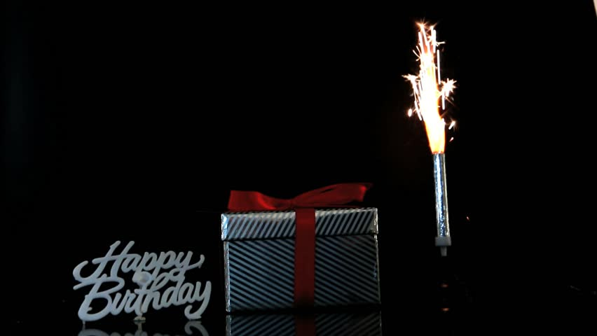 Sparkler Burning Beside Gift And Happy Birthday Sign On