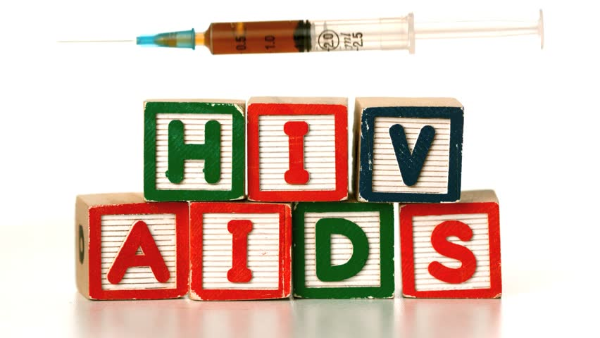 Needle falling on blocks spelling AIDS and HIV in slow motion - HD stock footage clip