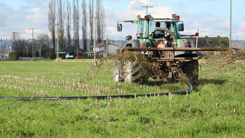 A farmer fertilizes his field in anticipation of S[ring planting/Fertilizing Field/Machines are used to spread manure over a field