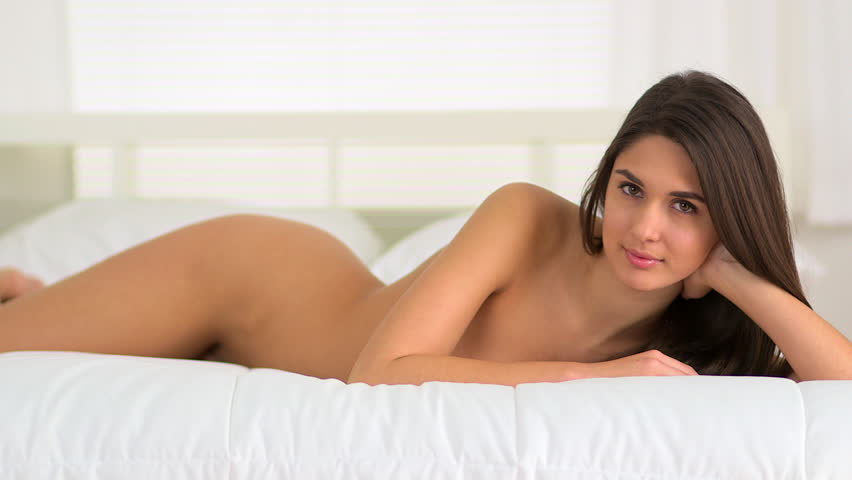 Nude woman smiling on bed