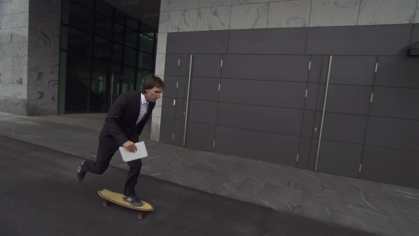 Young businessman skateboarding to work - HD stock video clip