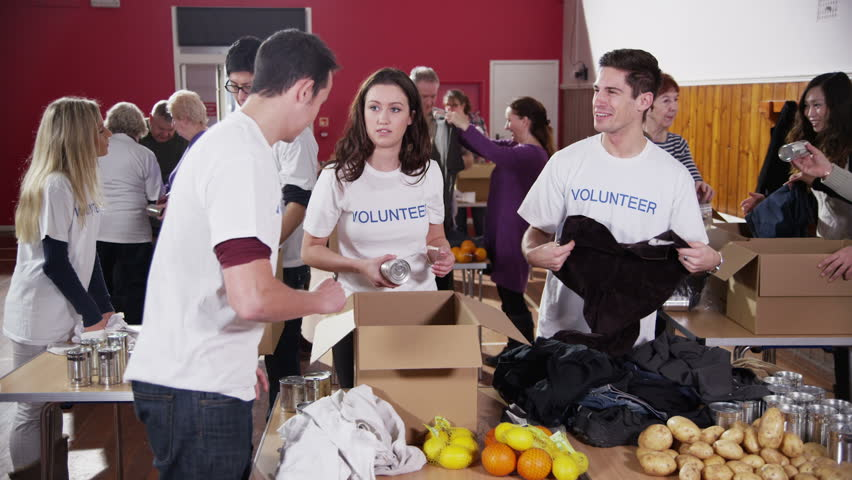 As charity workers and members of the community work together filling boxes with food and clothing, one male volunteer comes to the front of the shot and smiles at the camera. In slow motion.