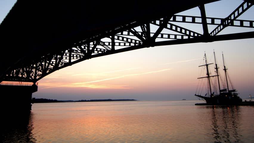 Sunrise time-lapse under bridge with sailing ship