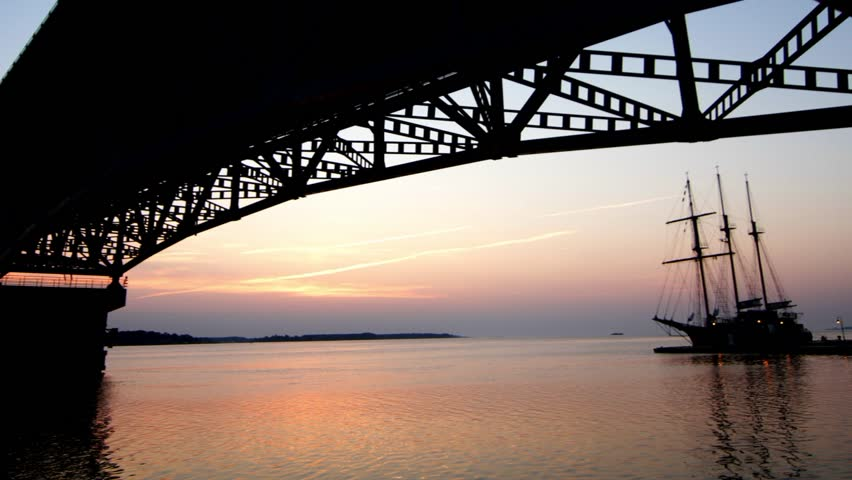 Sunrise time-lapse under bridge with sailing ship