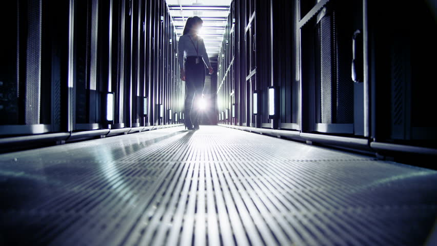 Attractive female IT engineer is working in a data centre with rows of server racks and super computers. She is walking up and down and checking all of the equipment.