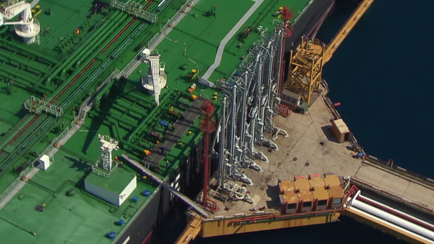 Aerial helicopter shot of a tanker with its mechanization in LNG terminal - HD stock footage clip