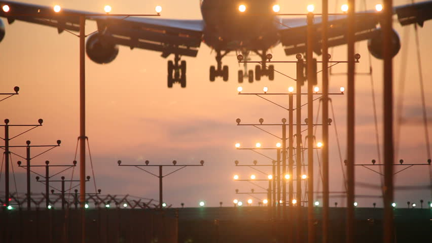 Big airplane plane landing in airport at sunset