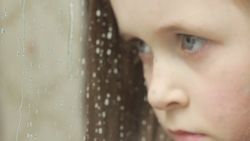 Child sad / bored - a little girl looks sadly out of the window on a rainy day - HD stock video clip
