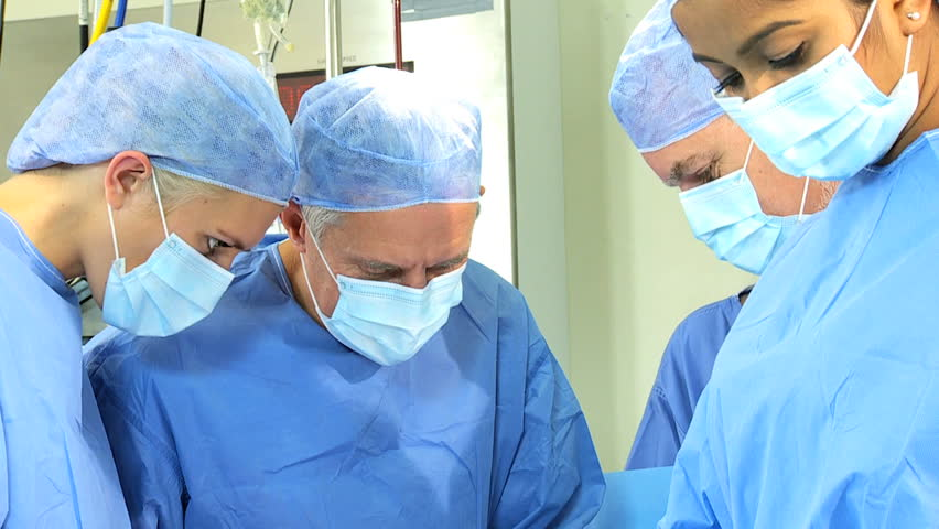 Skilled multi ethnic medical professionals close up performing surgery in sterile surroundings