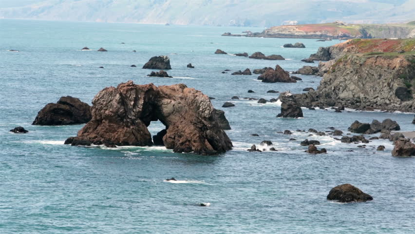 California coast arch rock in Pacific Ocean. Coastal California ocean beach, cliff and beautiful scenery along highway 101. Blue water waves crashing along beach and rocks. Incredible nature at work. - HD stock video clip
