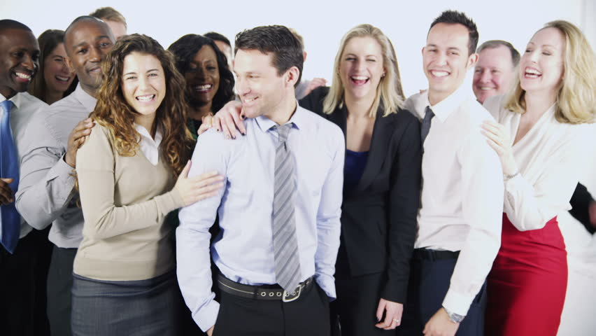 Portrait of a group of happy and diverse business people isolated on white in a studio shot. One man stands at the front and the rest of his team stand behind him, applauding his success.