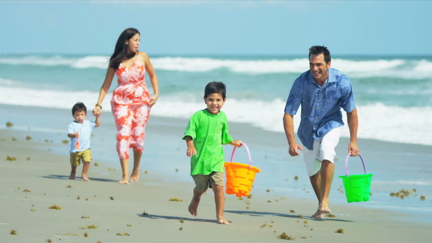 Loving Hispanic parents running with little children in ocean surf shot on RED EPIC - HD stock video clip