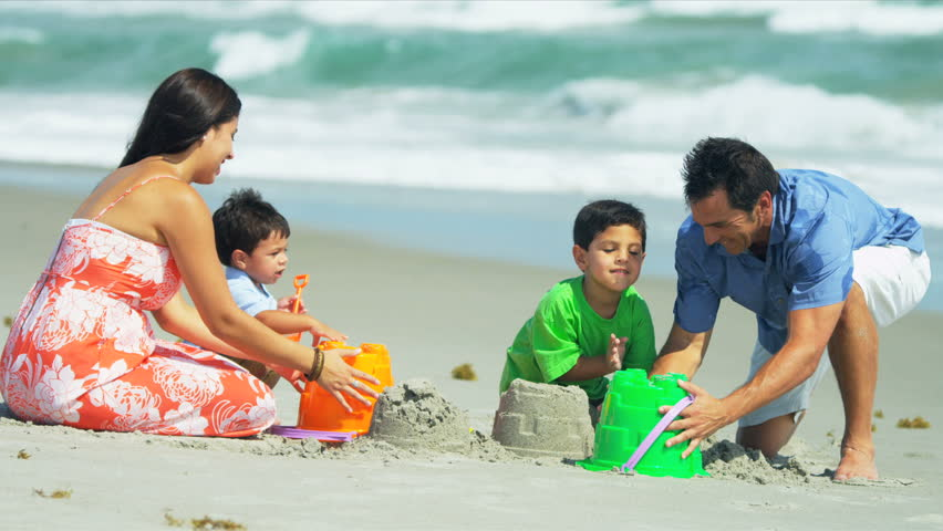 Happy Hispanic parents helping kids with sand castles on beach shot on RED EPIC - HD stock footage clip