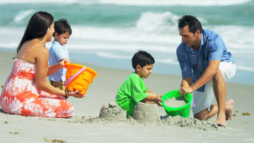 Little Latin American brothers playing together with loving parents by ocean shot on RED EPIC - HD stock video clip