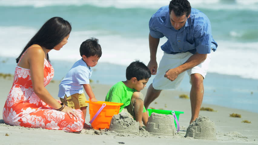 Happy Hispanic family building sand castles on beach shot on RED EPIC - HD stock footage clip