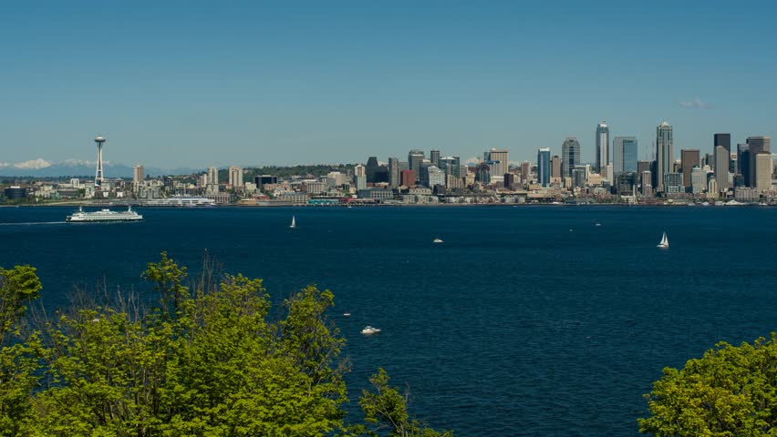 Elliot Bay and the Seattle waterfront with both commercial and recreational boats on the bay during a sunny spring day