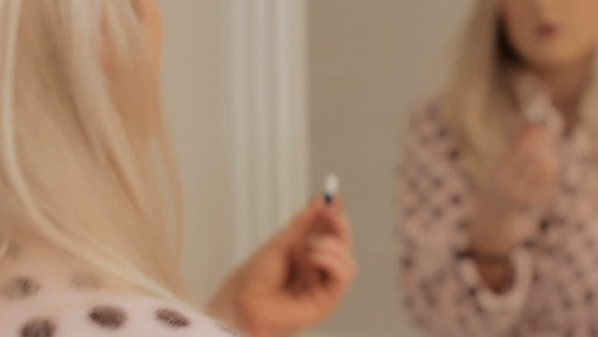 Taking Pills - a young woman taking pills in the bathroom