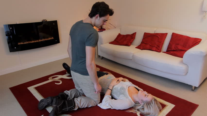 Recovery Position - A man places an unconscious woman into the Recovery Position, checking her airway