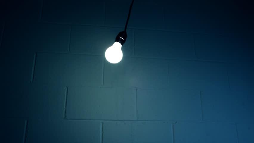 Swinging Light Bulb in Dark Room