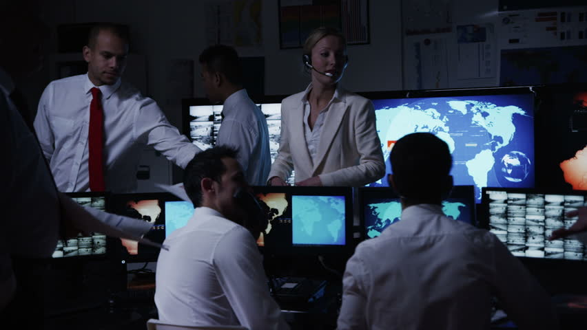 A team of security personnel working in a busy system control room, could be a weather station/airport traffic control. It could be a  power station or police/army control facility.