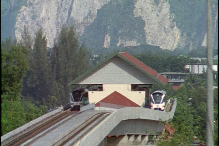 KUALA LUMPUR - OCTOBER 25, 1999: Lake Garden tram station. Train leaves station on elevated track and heads towards camera. Camera tilts up slightly to show mountains in background.