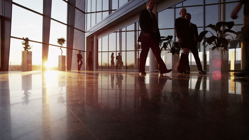 A diverse group of business people are making their way around a busy modern office building as the sun sets outside.