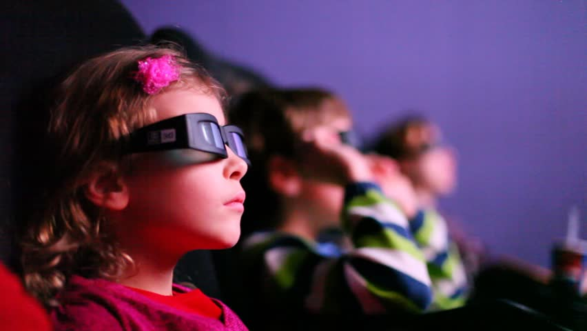 Three kids looking to a 3D movie smiling - HD stock footage clip
