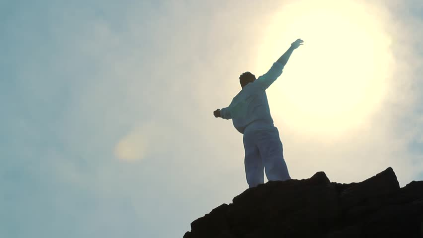 Worship Pose Silhouette of Man on Mountain Peak Raising Religious Arms at Sun
