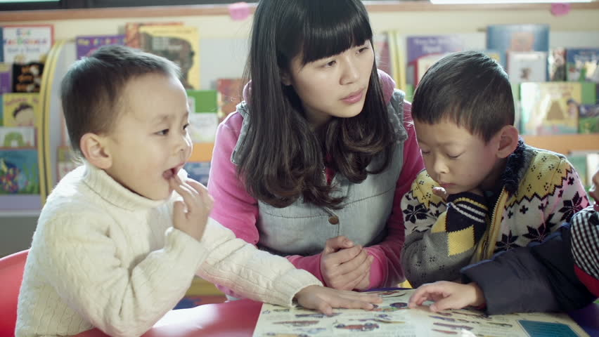 asian kindergarten teacher and her students sit at a small table reading a book together in a classroom in china. dolly shot.