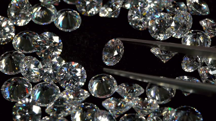 Selecting a Clear White Diamond With Pincers.
