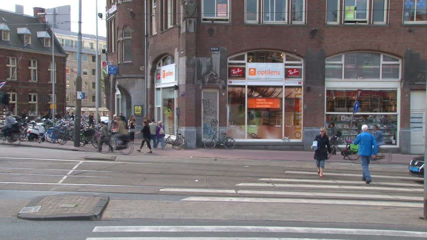 AMSTERDAM, NETHERLANDS - MAY 2012: Tram stops for a pedestrian on a crossing in Amsterdam city center. - HD stock video clip