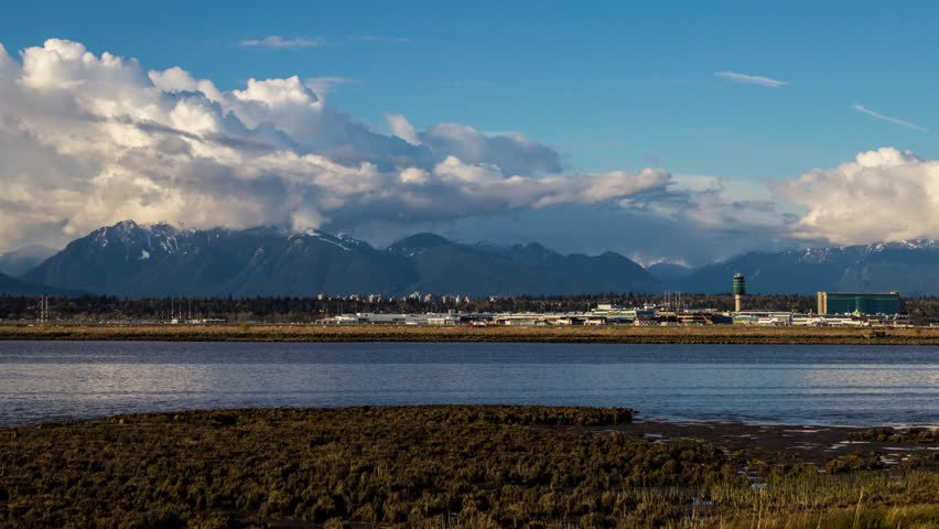 Time Lape of YVR (Vancouver International Airport) traffic with cloudy sky background as it getting low tide