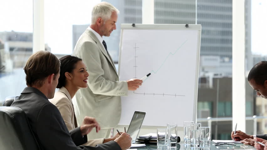 Businessman presenting to the team taking notes in the boardroom