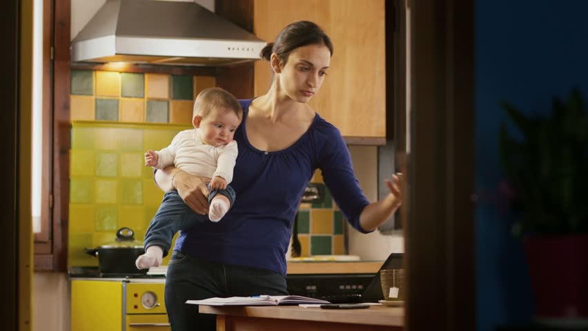Busy woman talking on the phone in kitchen, multi-tasking mom cooking and working, holding child at home