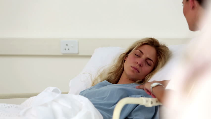 Nurse comforting unwell patient in hospital ward - HD stock video clip