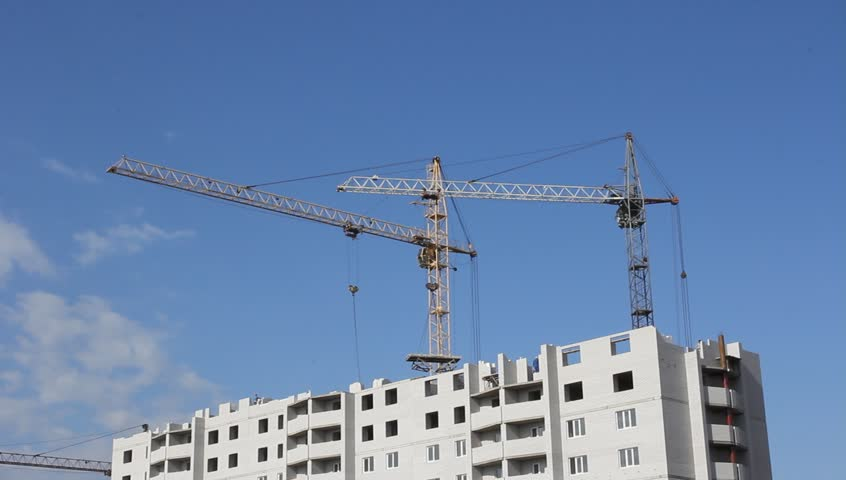 Tower cranes against blue sky, with clouds. Two shots - HD stock video clip