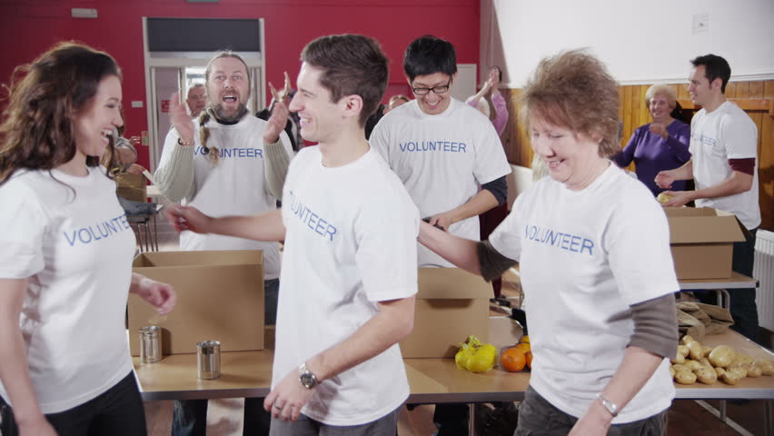 One male and two female charity volunteers of mixed ages put their arms around each other and give big smiles into the camera. Their fellow volunteers applaud and cheer in the background. Slow motion.