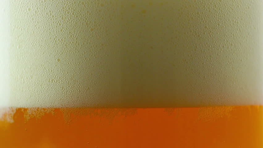 Beer being poured into translucent glass, white isolated background, detailed