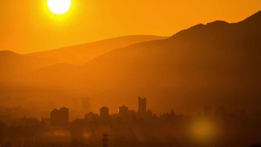 Sunset time with misty fog above buildings. Photo Sequence shot on DSLR camera, and post production in After Effects