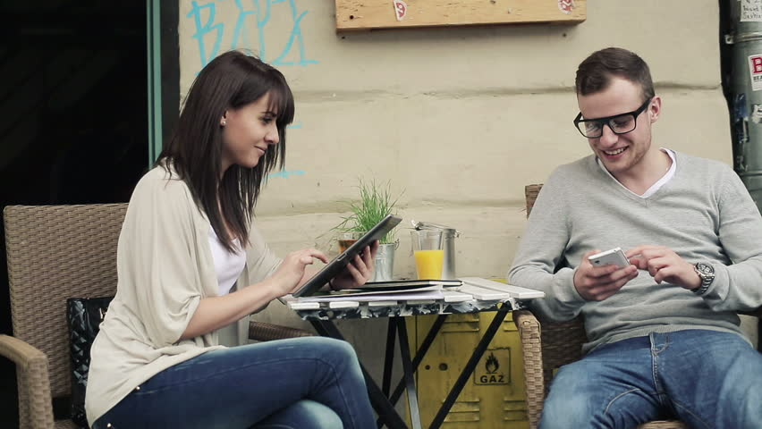 Happy couple with smartphone and tablet in cafe, steadicam shot - HD stock video clip