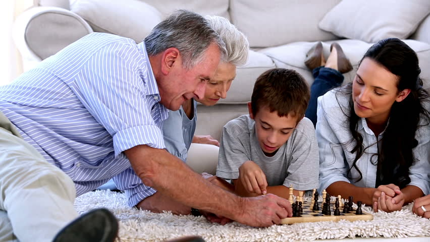 Extended family playing chess together on the floor at home - HD stock video clip